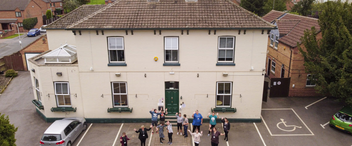 Aerial shot of Homefield College main site, with staff and students standing in front waving