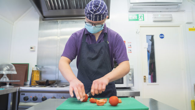Student chopping tomatoes in commercial kitchen