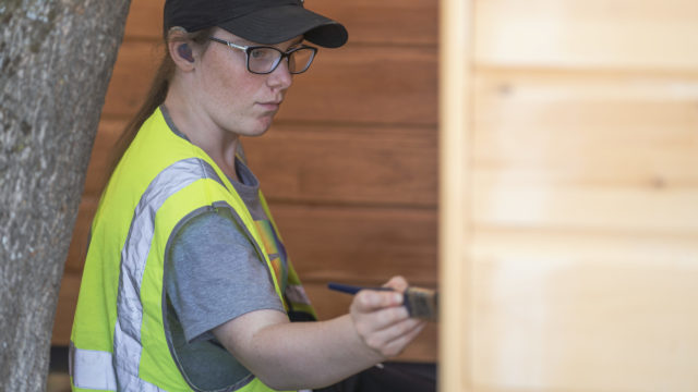 Student working outside painting wooden building