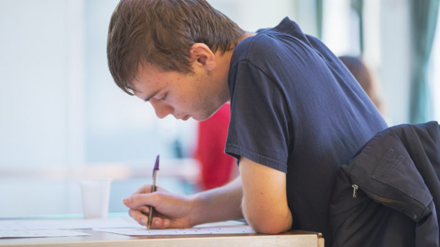 Student at desk holding pen concentrating on worksheet