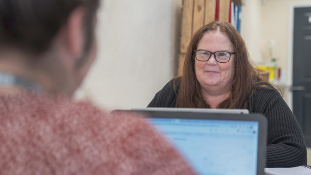 Staff member smiling across the laptop at another person