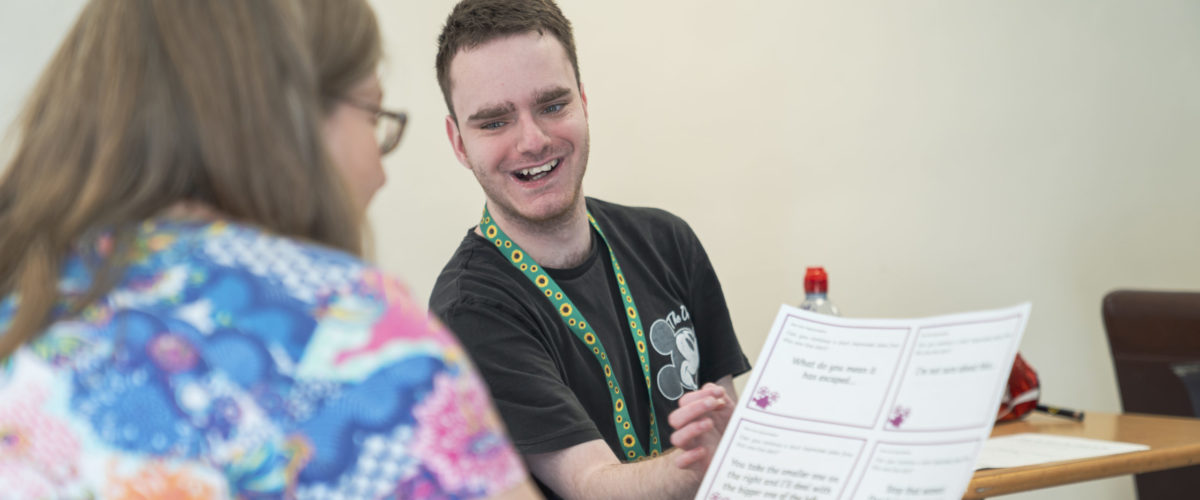 Student smiling whilst showing a document to a staff member