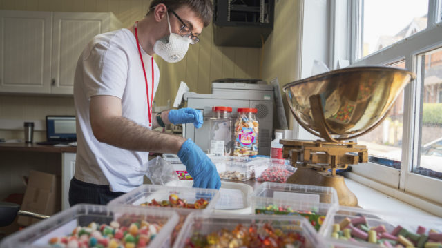 Student working in the sweet shop weighing sweets