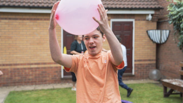 Student catching a balloon in the garden