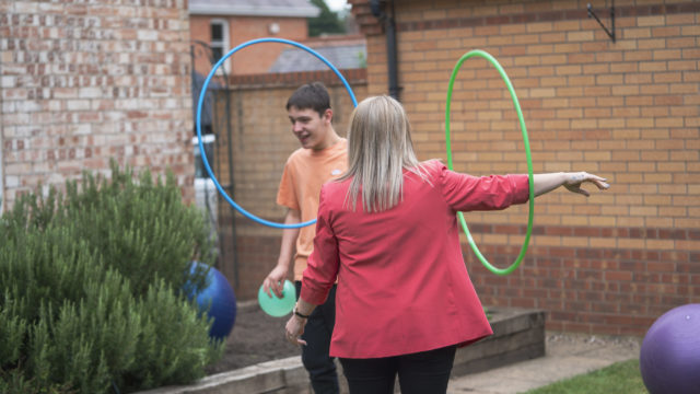 Student and staff playing with hula-hoops