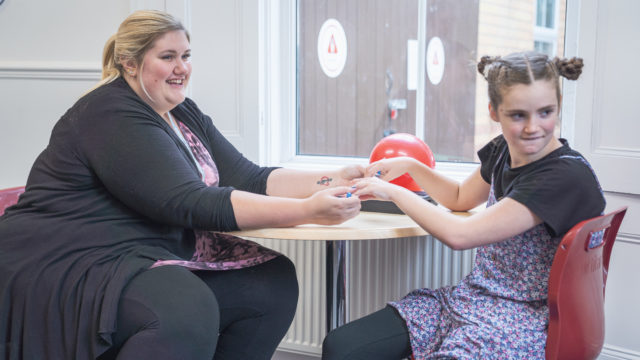 Learning Support Assistant performing massage on student hands
