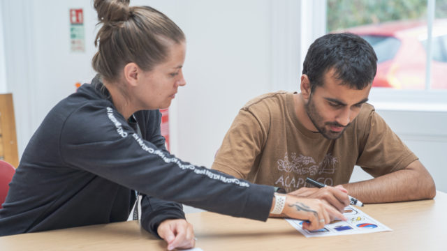 Learning Support Assistant helping a student with their worksheet
