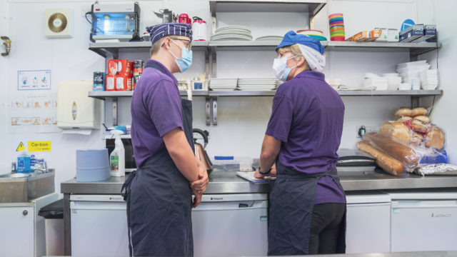 Student and staff conversing in commercial kitchen