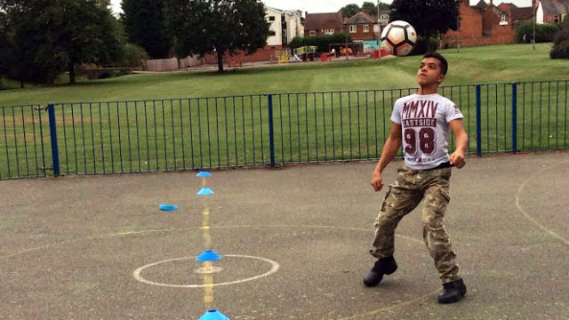 Student playing keepy-uppy with a football