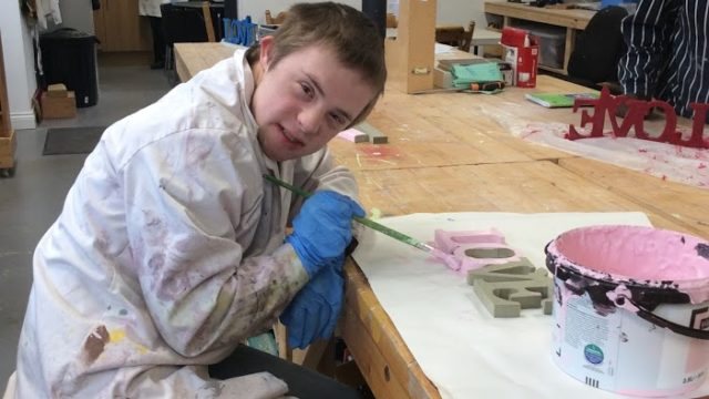 Student smiling whilst painting a wooden ornament saying love