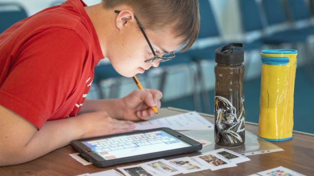 Student using ipad to help answer worksheet