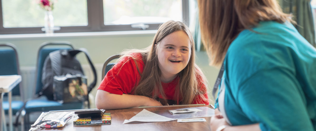 Student grinning whilst talking to a Learning Support Assistant