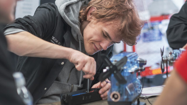 Student using tools on practice engine parts