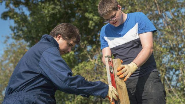 Students using level measure on fencepole